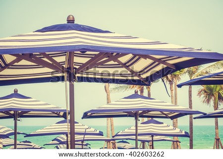 Colorful umbrella beach on sky background - Vintage Filter - stock photo