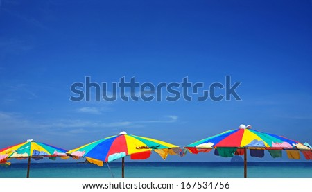 colorful umbrella beach on sunny summer day - stock photo