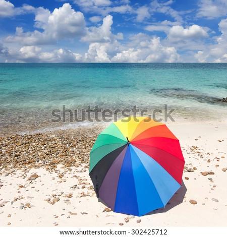 Colorful umbrella on the beach, blue sky. - stock photo