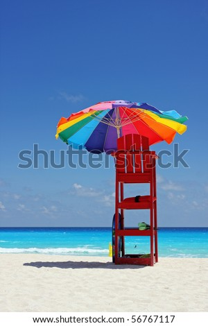 Colorful umbrella on white Caribbean beach - stock photo