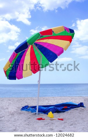 Colorful umbrella with toys and towel at beach - stock photo