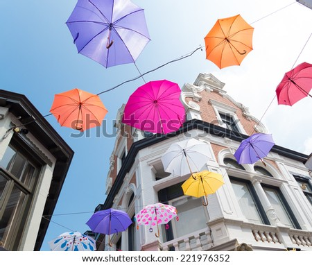 "Colorful umbrellas above the streets  during ""Deventer on stilts"", one of the most prestigious outdoor theatre festivals in the country - stock photo"