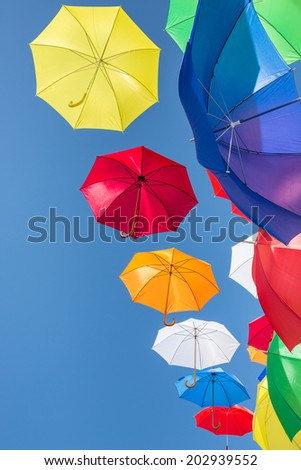 Colorful umbrellas hanging in in a clear blue sky - stock photo