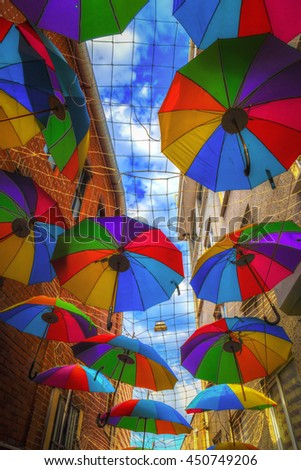Colorful umbrellas hanging over the street with blue sky, saturated image - stock photo