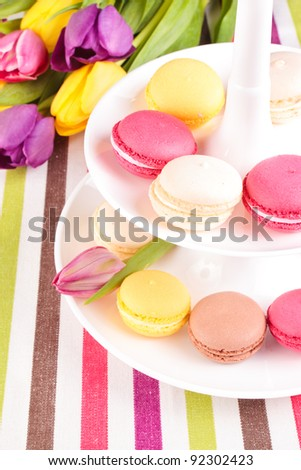 Colorful variety macaroons with tulips bouquet - stock photo
