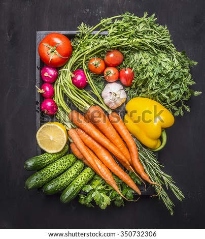 Colorful various of organic farm vegetables with fresh carrots with cherry tomatoes, garlic, lemon radish, peppers, cucumbers on wooden rustic background top view - stock photo