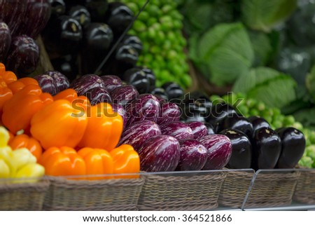 Colorful vegetables in the super market or a store in basket. Orange bell pepper, eggplants and green salads - stock photo