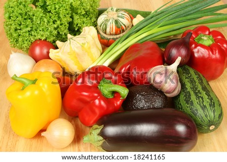Colorful vegetables on a wooden table. Peppers, zucchini, onions and others.