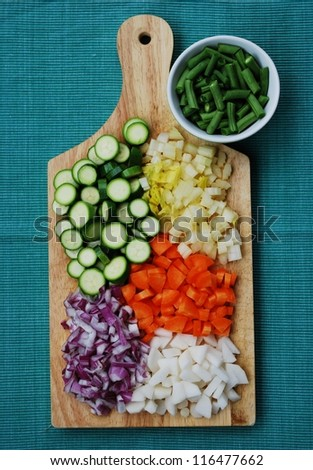 Colorful vegetables palette on wooden trencher on green background - stock photo