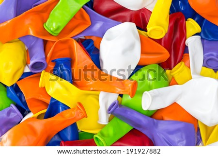 Colorful vibrant background of a pile of deflated party balloons in the colors of the rainbow or spectrum for a festive occasion or holiday celebration - stock photo