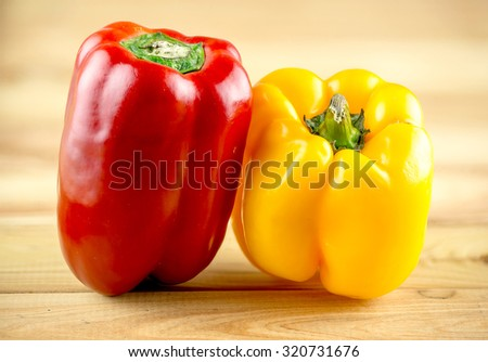 Colorful, vibrant red and yellow capsicum on wooden chopping block - stock photo