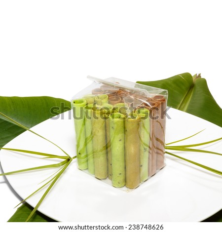 Colorful waffle rolls packed in transparent plastic bag on a white plate and a leaf - stock photo