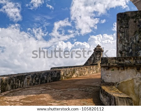 Colorful wall at the El Morro with the blue green atlantic ocean in the background with beautiful puffy streaked white clouds