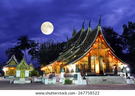 Colorful Wat Xieng thong temple at dusk in Luang Prabang, Loas - stock photo