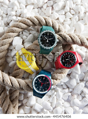 colorful watches on the stones with a rope for boats - stock photo