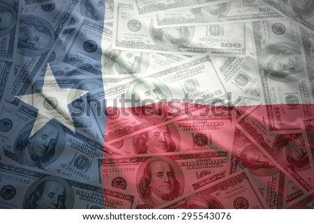 colorful waving texas state flag on a american dollar money background - stock photo