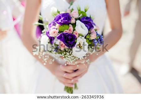 Colorful wedding bouquet in bride's hands with eustomas and alstromeria - stock photo