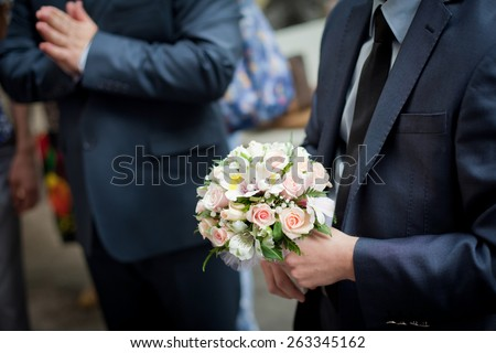 Colorful wedding bouquet with roses  in groom's hands - stock photo