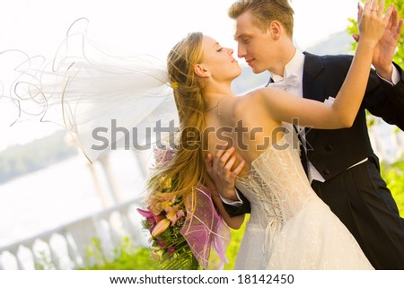 Colorful wedding shot of bride and groom kissing - stock photo