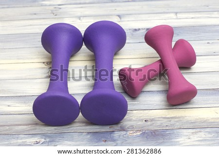 Colorful weights on a wooden background - stock photo