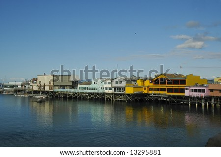 Colorful wharf at Monterey, California, with bright blue sky and water - stock photo