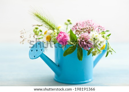 Colorful wildflowers in watering can on wooden table - stock photo