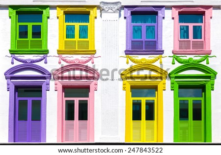 Colorful windows and white building facade. - stock photo