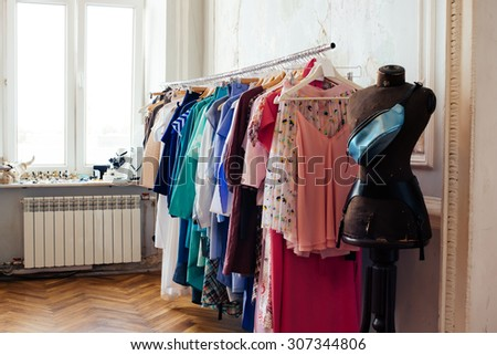Colorful women's dresses on hangers in a retail shop. Fashion and shopping concept - stock photo