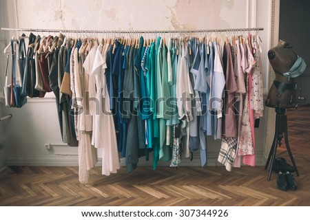 Colorful women's dresses on hangers in a retail shop. Fashion and shopping concept. Toned picture - stock photo