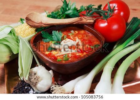 Colorful wooden bowl of Chicken Tortilla Soup with the fresh ingredients deconstructed around the serving. - stock photo