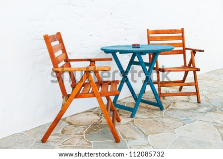 Colorful wooden chair and table arrangement from a Greek island alleyway - stock photo