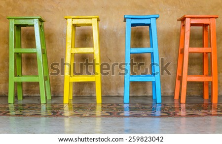 Colorful wooden chairs arranged tall. - stock photo