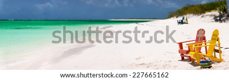 Colorful wooden chairs at tropical white sand beach in Caribbean, panorama with copy space perfect for banners - stock photo