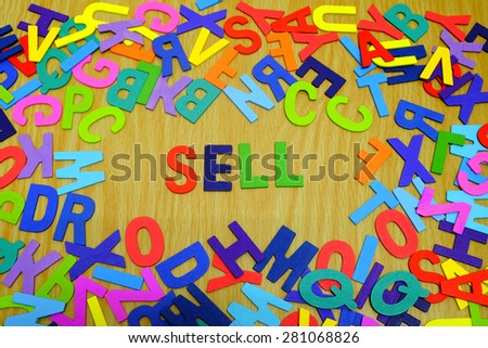 Colorful Wooden SELL alphabet letters and background texture of wood.  Concept of Government Service Tax. Slightly defocused and close-up shot.