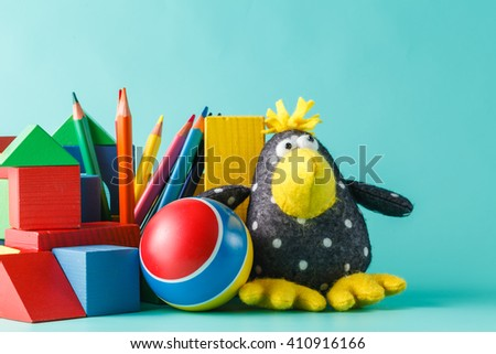 Colorful wooden toy building blocks with toys on aquamarine - stock photo