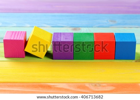 Colorful wooden toy cubes on a colorful wooden background - stock photo