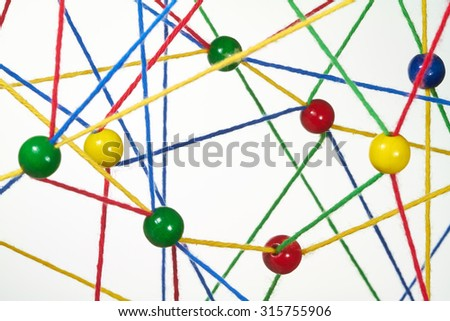Colorful wool threads form a network between colorful balls. - stock photo