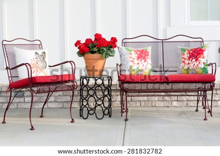 Colorful wrought iron garden furniture with vibrant red cushions and a red potted geranium standing on an open-air front patio or porch ready for the warm spring and summer weather - stock photo