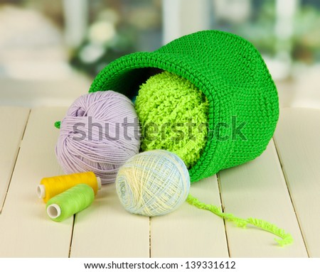 Colorful yarn for knitting in green basket on wooden table on window background - stock photo