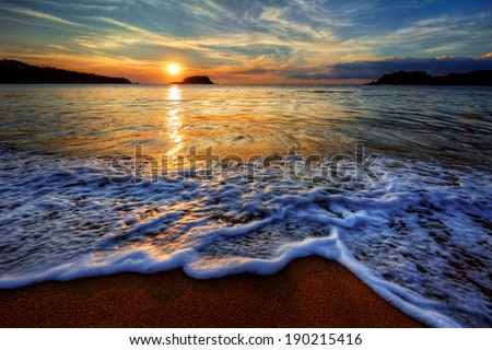 Colorful yellow and blue ocean bay sunset with sea foam - stock photo
