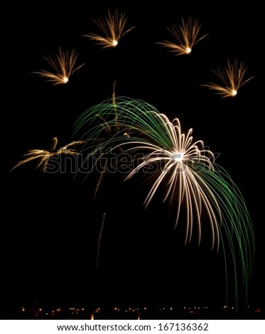 Colorful yellow and green colors, amazing fireworks explosion in dark sky background, 4 of July, Independence day, explode, fireworks festival fragment close up with village silhoutthe on the bottom - stock photo