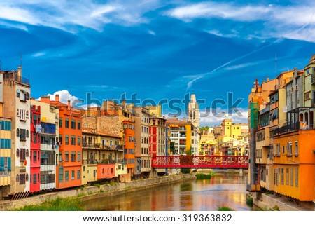 Colorful yellow and orange houses and Eiffel Bridge, Old fish stalls, reflected in water river Onyar, in Girona, Catalonia, Spain. Church of Sant Feliu at background. - stock photo