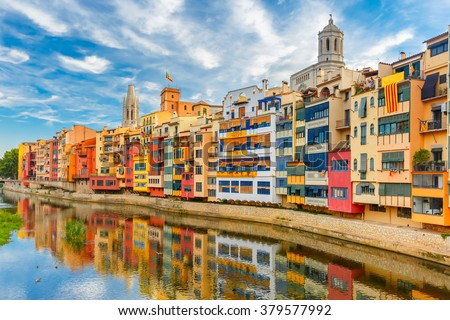 Colorful yellow and orange houses and famous house Casa Maso reflected in water river Onyar, in Girona, Catalonia, Spain. Church of Sant Feliu and Saint Mary Cathedral at background. - stock photo