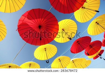 colorful yellow and red  umbrellas under the beautiful cloudy sk