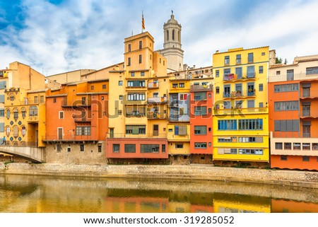 Colorful yellow, red and orange houses with the Catalan flag reflected in water river Onyar, in Girona, Catalonia, Spain. Saint Mary Cathedral at background. - stock photo
