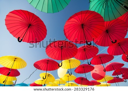 colorful yellow, red, blue and green  umbrellas under the beautiful cloudy sky - stock photo