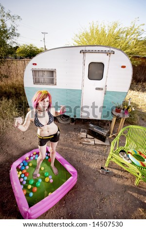 Colorful young woman flexing in a play pool