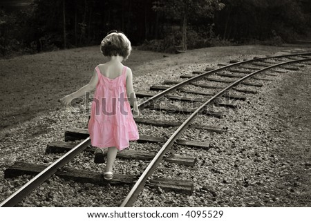 Colorized black and white with little girl in a pink dress walking on railroad track