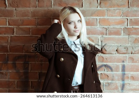 Colorized image of young hipster girl with long blond hair looking at camera copyspace on the red brick wall - stock photo