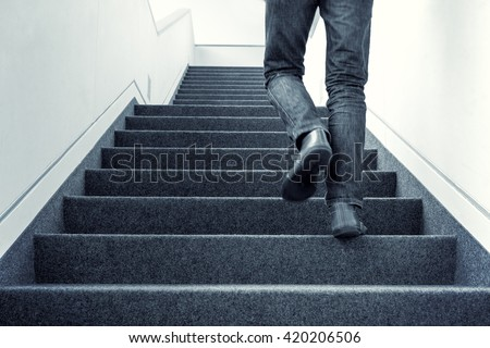 Colorized picture of one man walking upstairs on staircase indoors